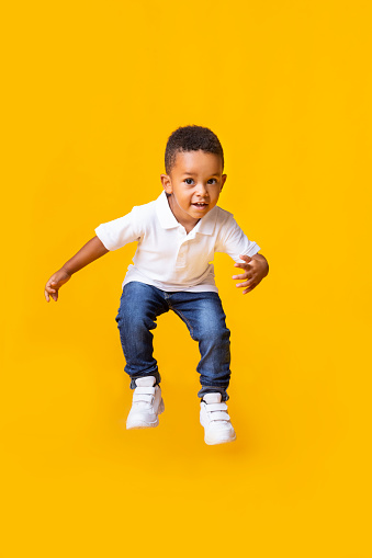 istock Adorable afro baby boy jumping over yellow studio background 1182627543