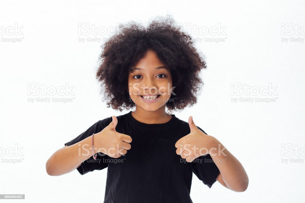 Adorable and cheerful African American kid with afro hairstyle giving thumbs up isolated over white background stock photo