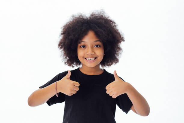 Adorable and cheerful African American kid with afro hairstyle giving thumbs up isolated over white background Adorable and cheerful African American kid with afro hairstyle giving thumbs up isolated over white background 12 13 years stock pictures, royalty-free photos & images