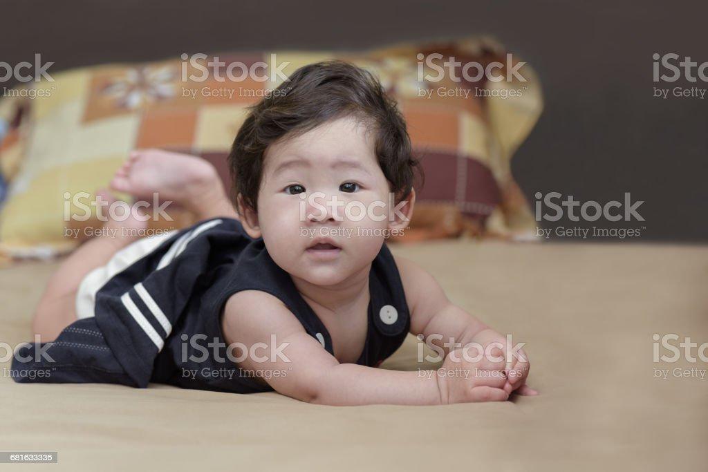 Adorable asian baby girl lying on bed. stock photo