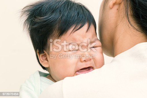 istock Adorable asian baby sick and crying on mom shoulder. (Vintage tone) 973975454