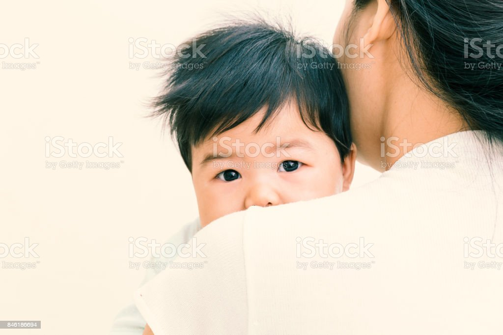 Adorable asian baby sick and unhappy on mom shoulder. (Vintage tone) stock photo