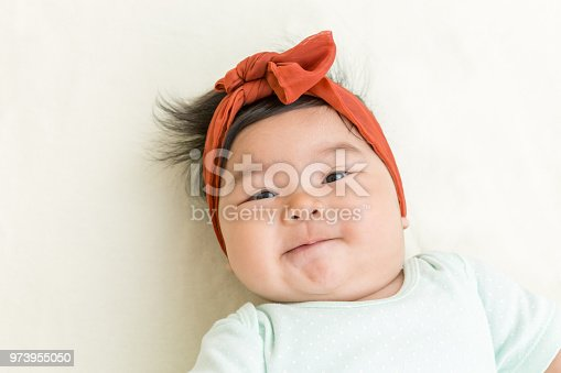 Adorable asian baby smiling on the bed.