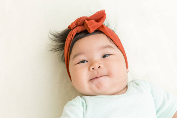 Adorable asian baby smiling on the bed. Adorable asian baby smiling on the bed. baby girls stock pictures, royalty-free photos & images