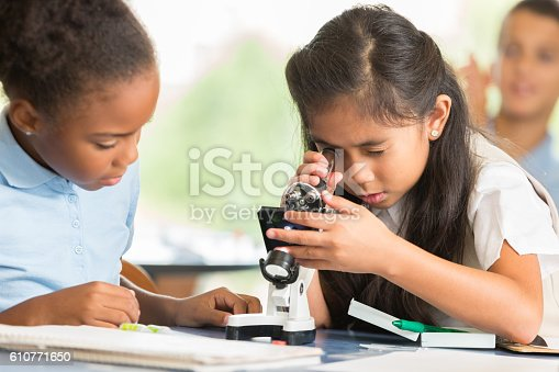 istock Adorable Asian girl uses microscope to study something 610771650