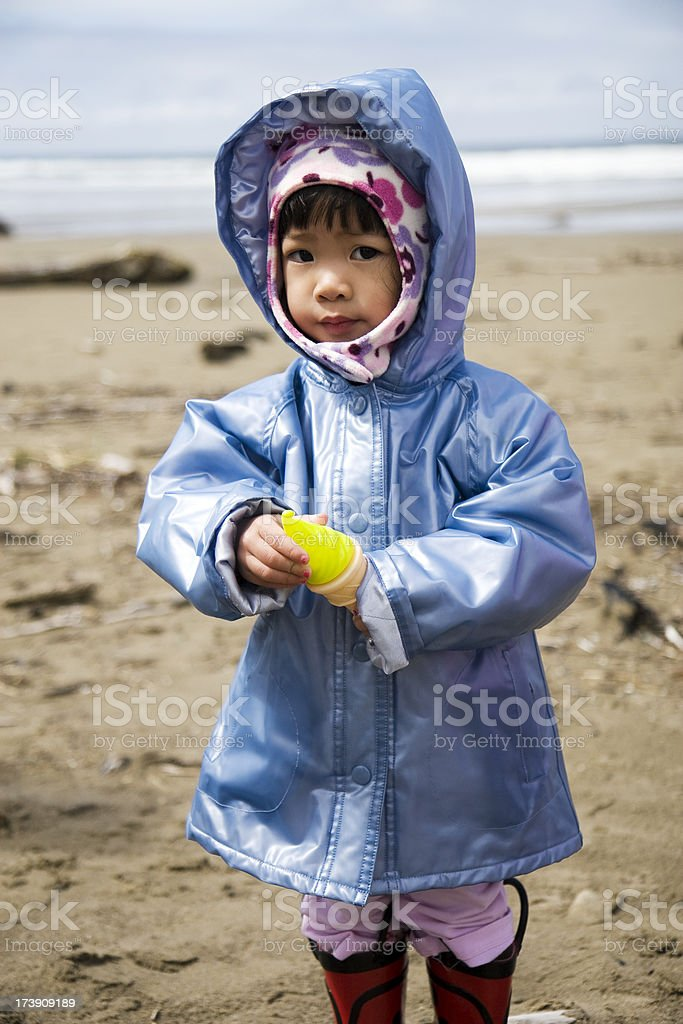 Adorable Asian Little Girl in Raincoat on Beach, Lifestyle Portrait royalty-free stock photo