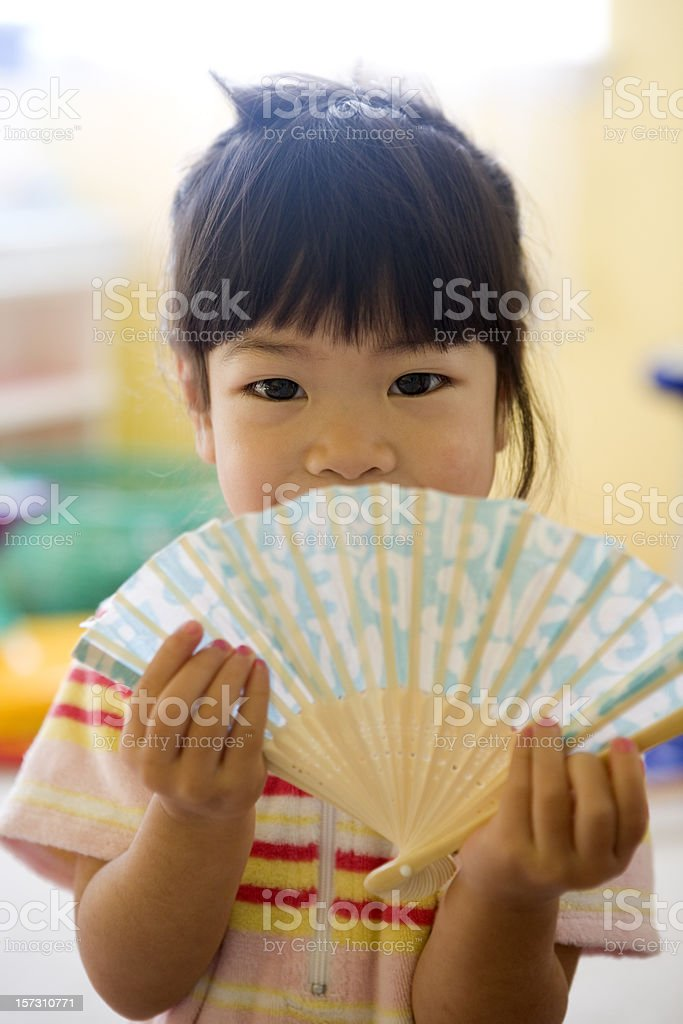 Adorable Asian Little Girl in Sunny Playroom Holding Alphabet Fan royalty-free stock photo