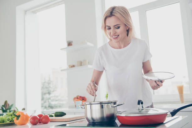 adorable attractive beautiful adult smiling cheerful woman wearing pajama white t-shirt cooking stirring food in pot with spoon. red tomatoes green salad chopped cucumber yellow pepper lying on table - woman cooking stock pictures, royalty-free photos & images