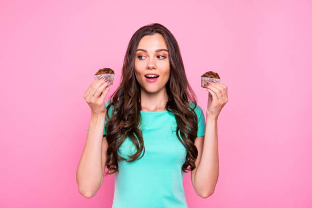 可愛迷人漂亮迷人的卷髮金髮女郎年輕的微笑的女孩舉行顯示兩個蛋糕的驚喜。查出的粉紅色蠟筆背景 - 即食口糧 個照片及圖片檔
