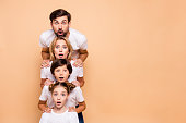 Adorable attractive surprised family, bearded father, blonde mother, boy and girl wearing white T-shirts, standing in odrer of hierarchy, holding hands on each other's shoulders. Copy space