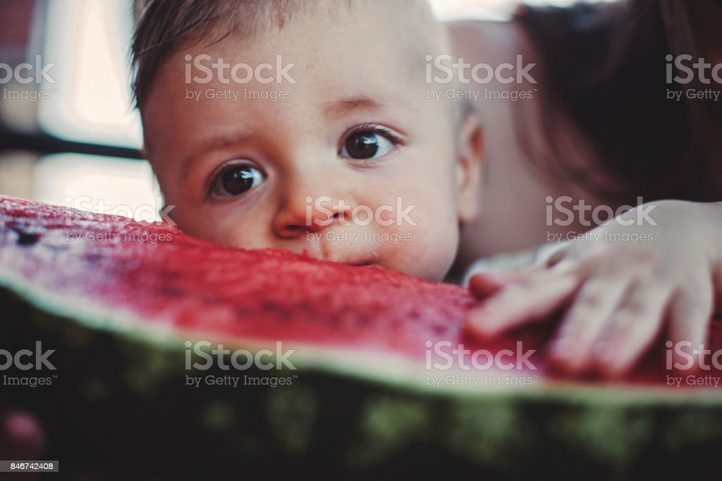 Adorable Baby Biting Watermelon stock photo