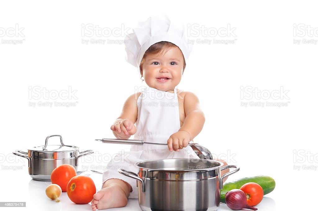 Adorable baby boy chef sitting and playing with kitchen equipment stock photo