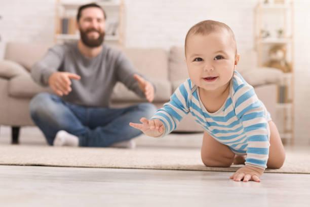 schattige baby jongen kruipen op de vloer met papa - background baby stockfoto's en -beelden