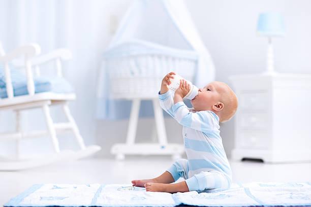 Adorable baby boy drinking milk in sunny nursery stock photo