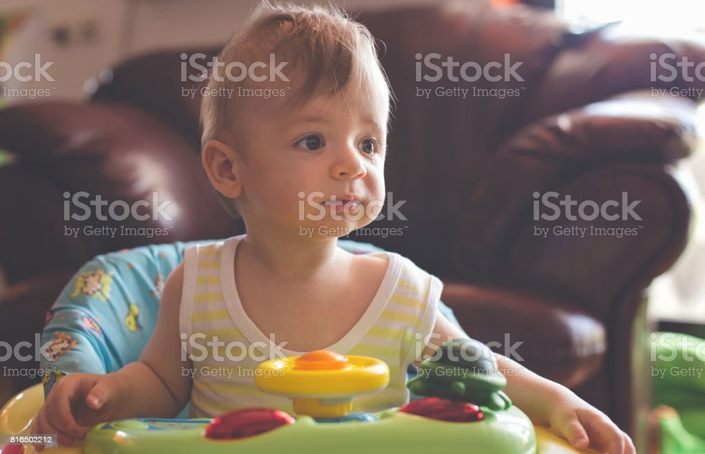 Adorable baby boy in baby walker stock photo