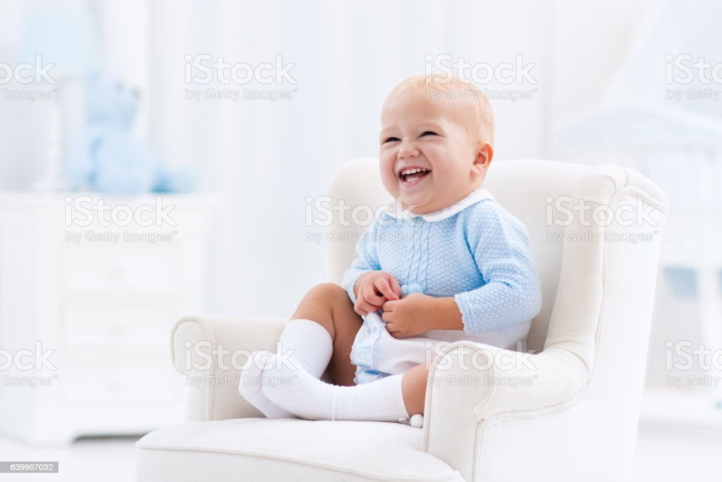 Adorable baby boy playing in bedroom stock photo