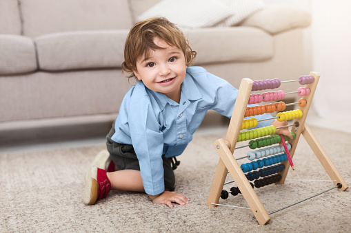 istock Adorable baby boy playing with colorful scores at home 1127322288