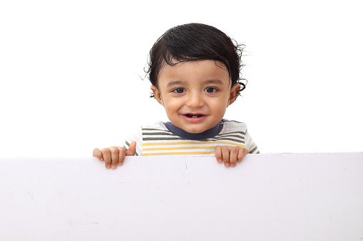 Adorable baby boy showing copy space on blank white board