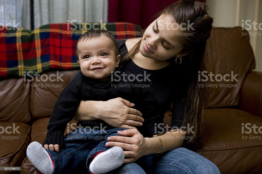 Adorable Baby Boy Sitting on Latina Mother's Lap at Home stock photo