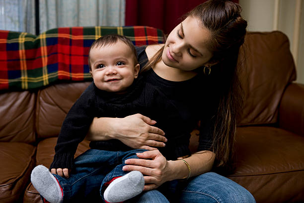 adorable baby boy sitzt auf latina mutters schoß wie zu hause fühlen. - sozialwohnung stock-fotos und bilder