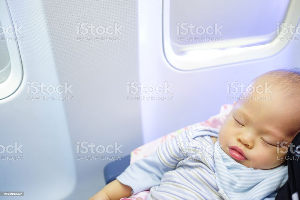 Adorable Baby Boy Sleeping in an Airplane on his mother's lap stock photo