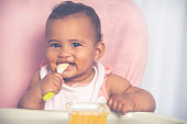 istock Adorable baby eating food by himself. 1327264365
