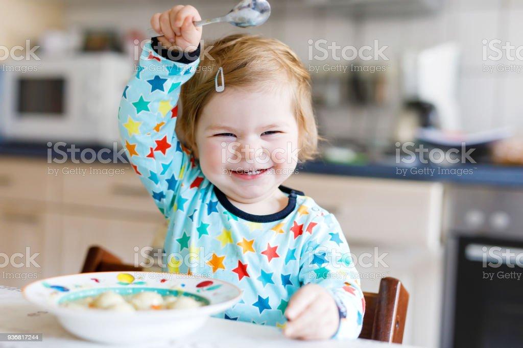 Entzückende Babymädchen Essen vom Löffel Gemüse Nudelsuppe. Essen, Kind, Fütterung und Leute Konzept – Foto