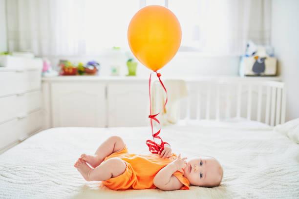 Adorable Babymädchen in orange Strampler Anzug mit bunten Ballons – Foto