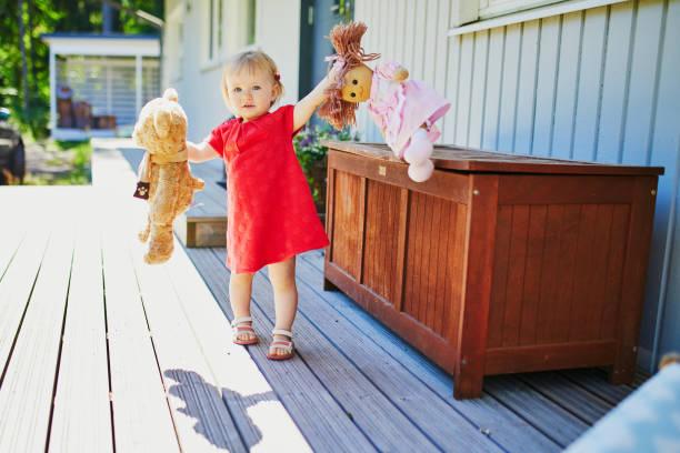 Entzückende Baby Mädchen in roten Kleid spielen mit Puppe und Teddybär – Foto