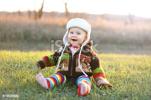 istock Adorable Baby Girl in Winter Hat and Sweater Laughing Outside 619539680