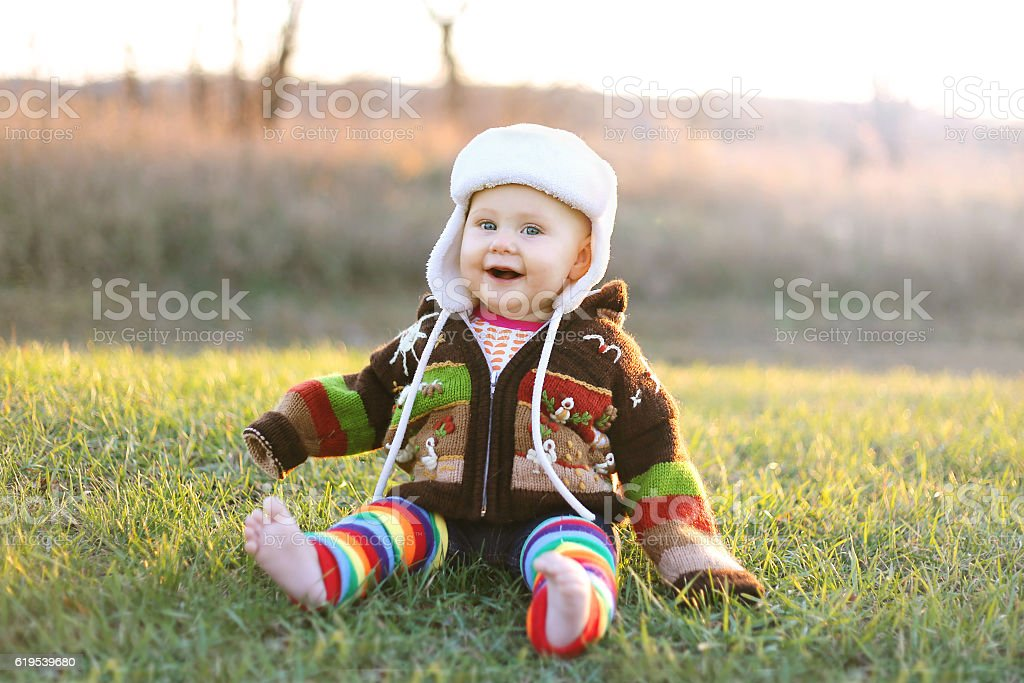 Adorable Baby Girl in Winter Hat and Sweater Laughing Outside stock photo