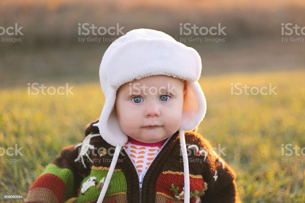 Adorable Baby Girl in Winter Hat and Sweater Outside stock photo
