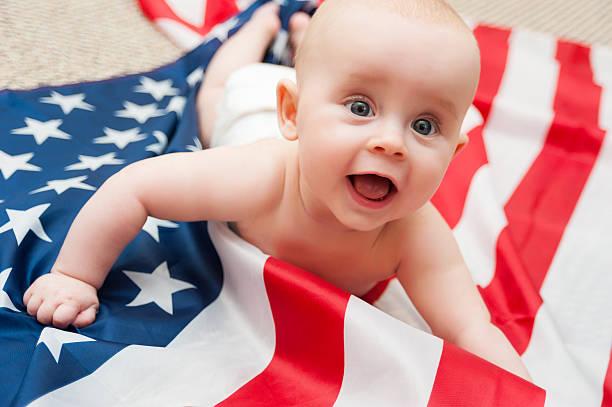 adorable baby girl lying on american flag background stock photo