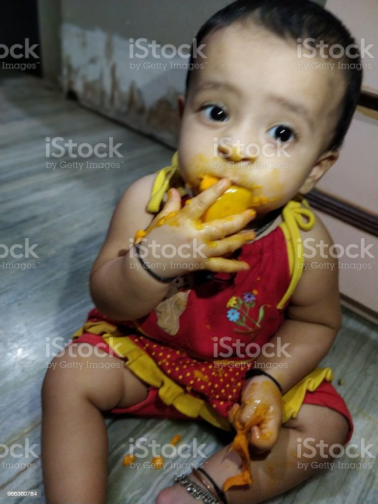 adorable baby girl making mess while feeding herself stock photo
