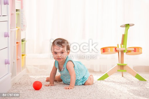 istock Adorable baby girl playing in the nursery. 841787438