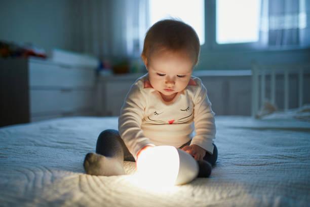 Entzückende Babymädchen spielen mit Nachttischlampe im Kindergarten – Foto