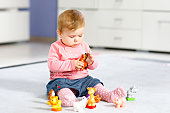 Adorable baby girl playing with domestic toy pets like cow, horse, sheep, dog and wild animals like giraffe, elephant and monkey. Happy healthy child having fun with colorful different toys at home