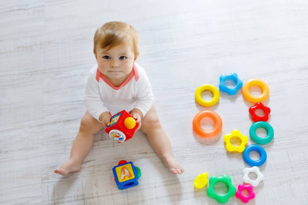 Adorable baby girl playing with educational toys in nursery stock photo