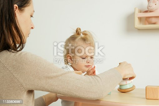 istock Adorable baby girl playing with her mum in the nursery room 1133806981