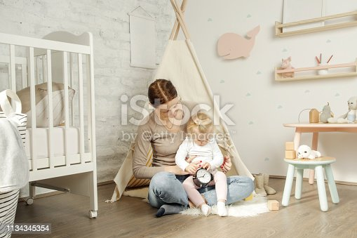 istock Adorable baby girl playing with her mum in the nursery room 1134345354