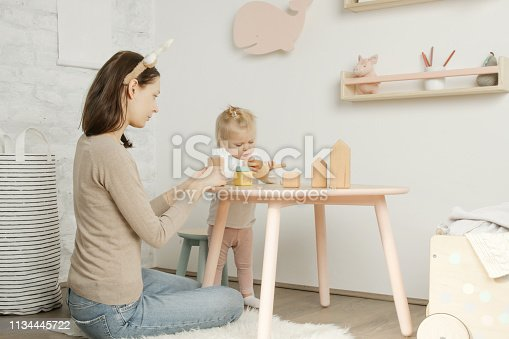 istock Adorable baby girl playing with her mum in the nursery room 1134445722