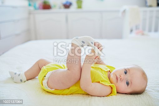 Adorable baby girl removing sock from her foot. Little child having fun. Infant kid in sunny nursery
