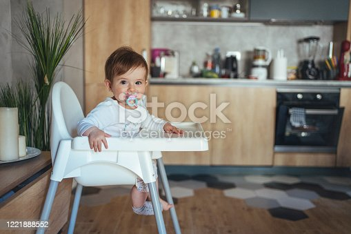 Cute 9 month's old baby girl sitting in the high chair, and with pacifier in her mouth looking around the house