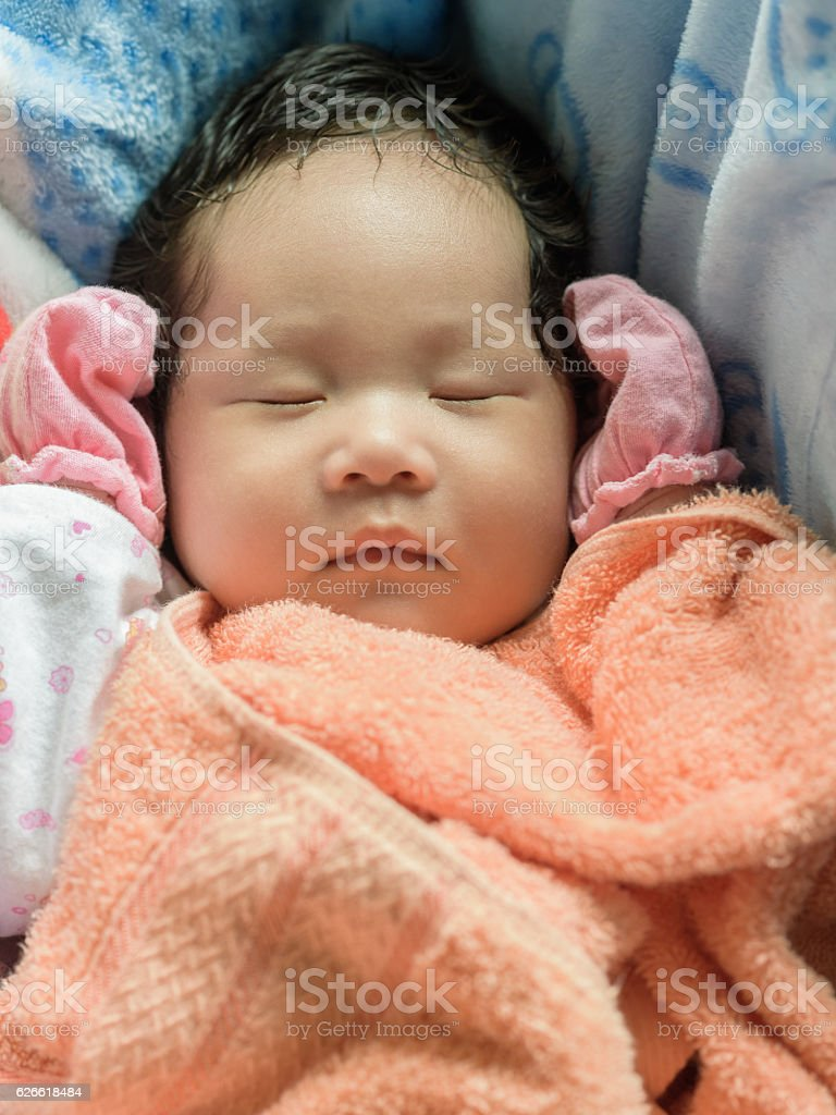 Adorable baby girl sleeping in blue bassinet. stock photo