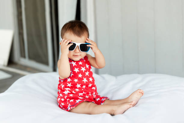 Adorable baby girl wearing red dress and sunglasses on Independence Day on 4th of July stock photo