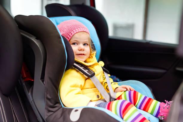 adorable petite fille aux yeux bleus et dans des vêtements colorés, assis dans le siège auto. enfant enfant en bas âge dans les vêtements d'hiver passait de voyage et vacances en famille. voyager en toute sécurité, sécurité enfants, transports - child car sleep photos et images de collection