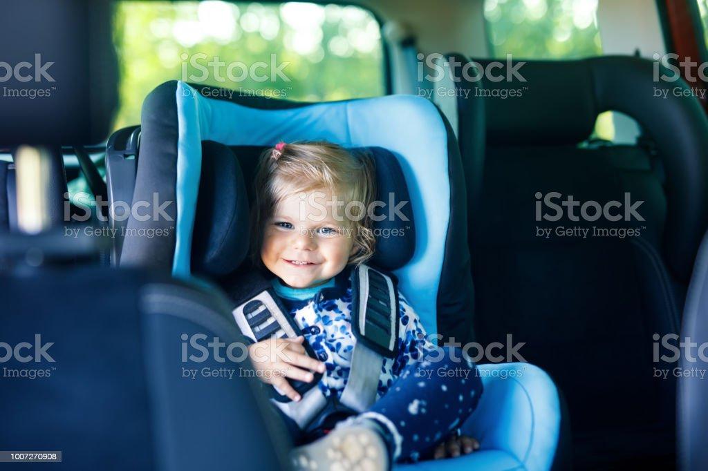 Entzückende Babymädchen mit blauen Augen, die im Kindersitz sitzen. Kleinkind Kind Ferien mit der Familie und die Reise geht. – Foto