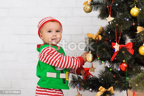 Xmas tradition. Adorable baby helping parents to decorate Christmas tree, free space