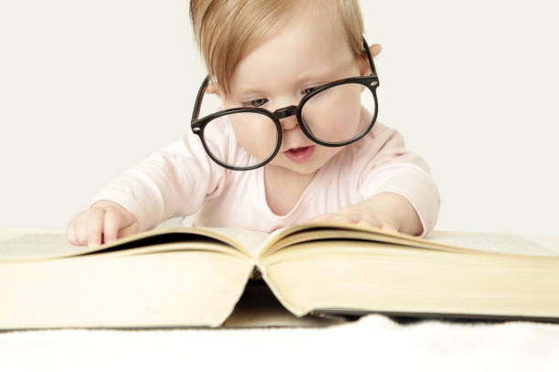 Adorable baby in front of big thick book, studio shot Adorable baby in front of big thick book, studio shot child prodigy stock pictures, royalty-free photos & images