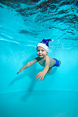 Adorable baby in hat of Santa Claus, with blue eyes swims underwater in the pool and looking at me. Portrait. Shooting under water. Vertical orientation.